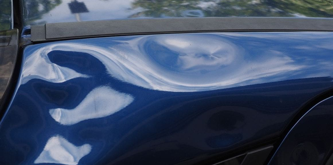 Many dents on blue car's body
